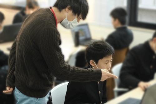 IT学習をする児童とそれを支援するスタッフ